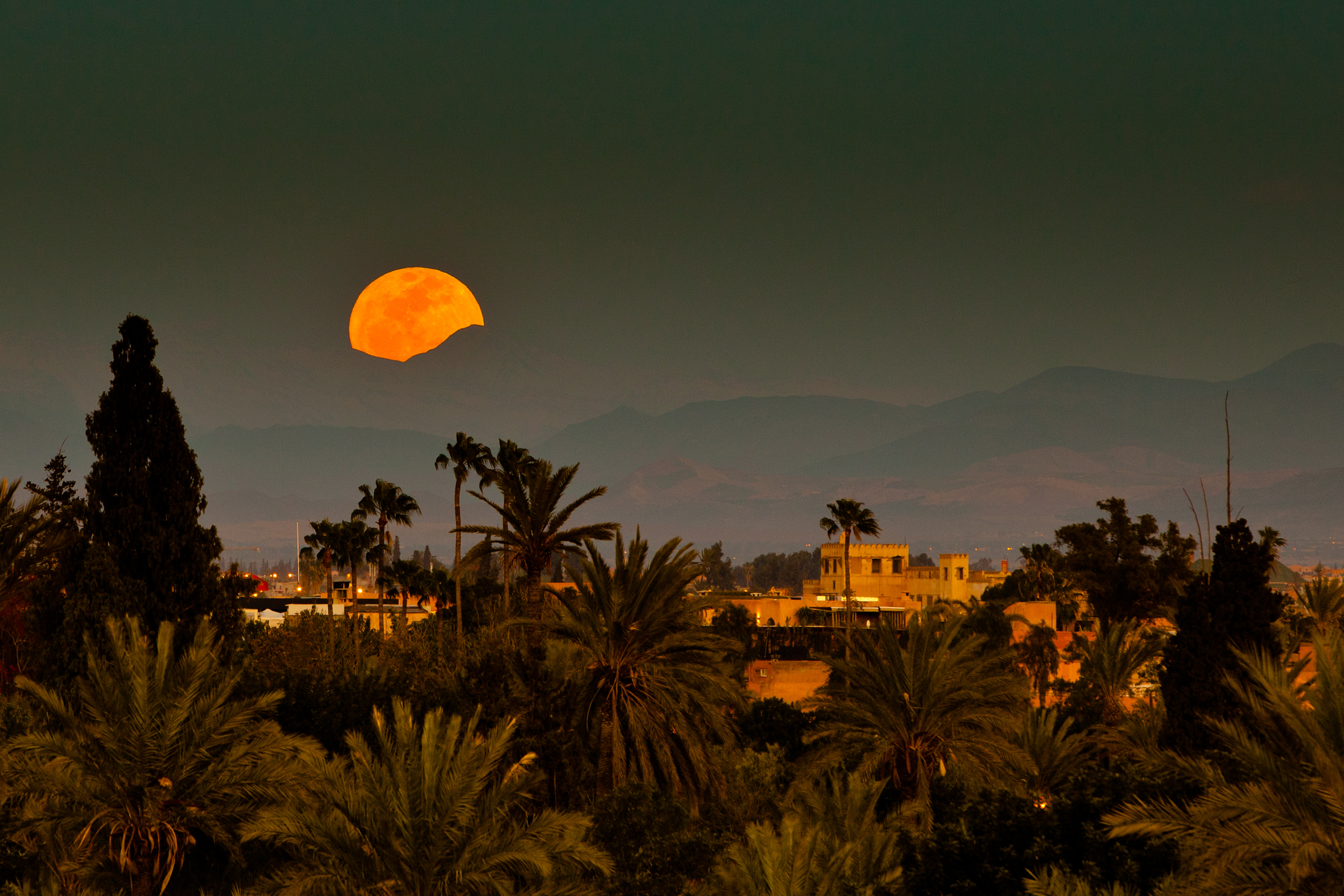 Moon rising in evening light, partly obscured by Atlas mountains.