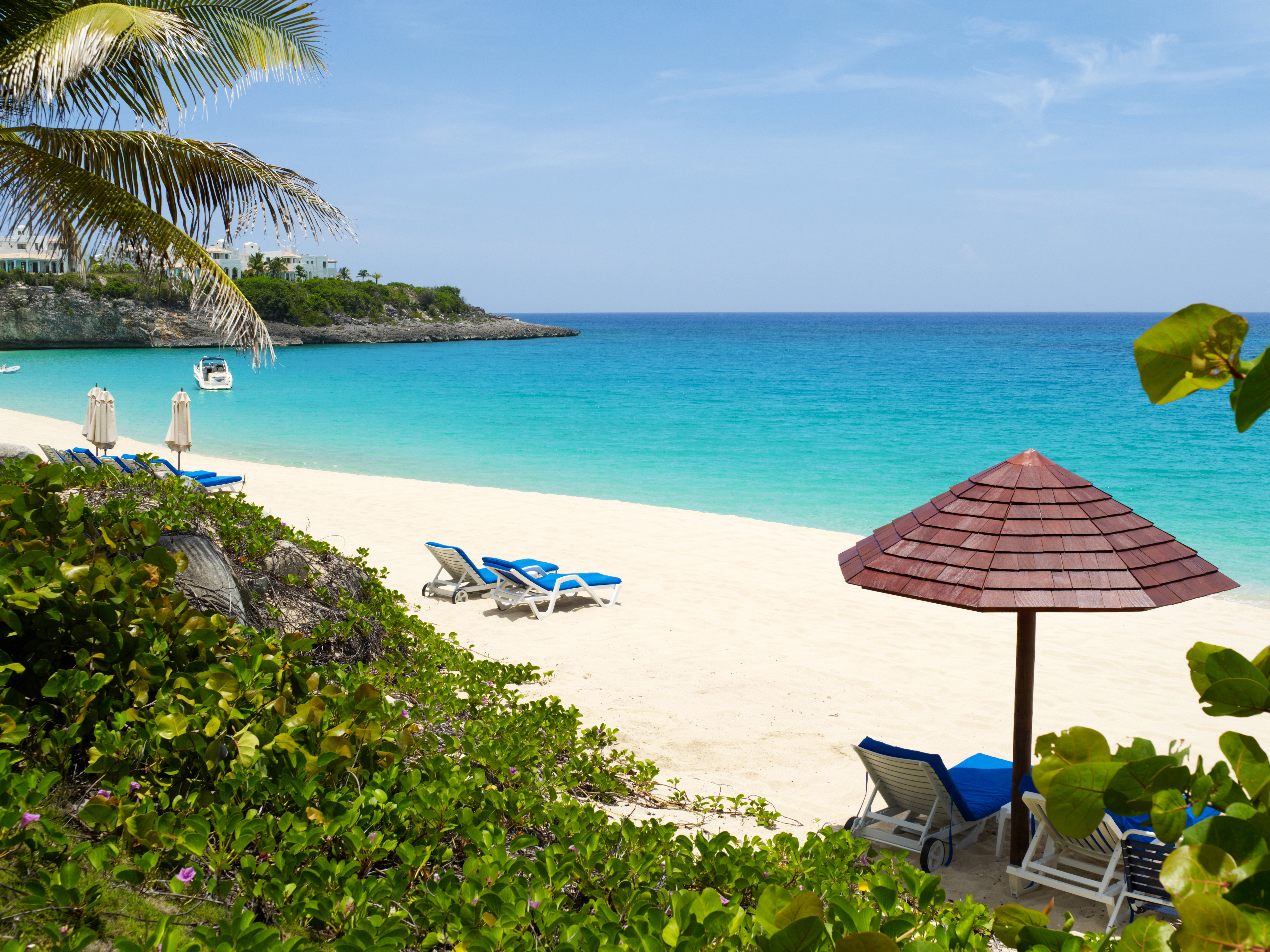 Luxury beach scene with lounge chairs and umbrella over looking island.