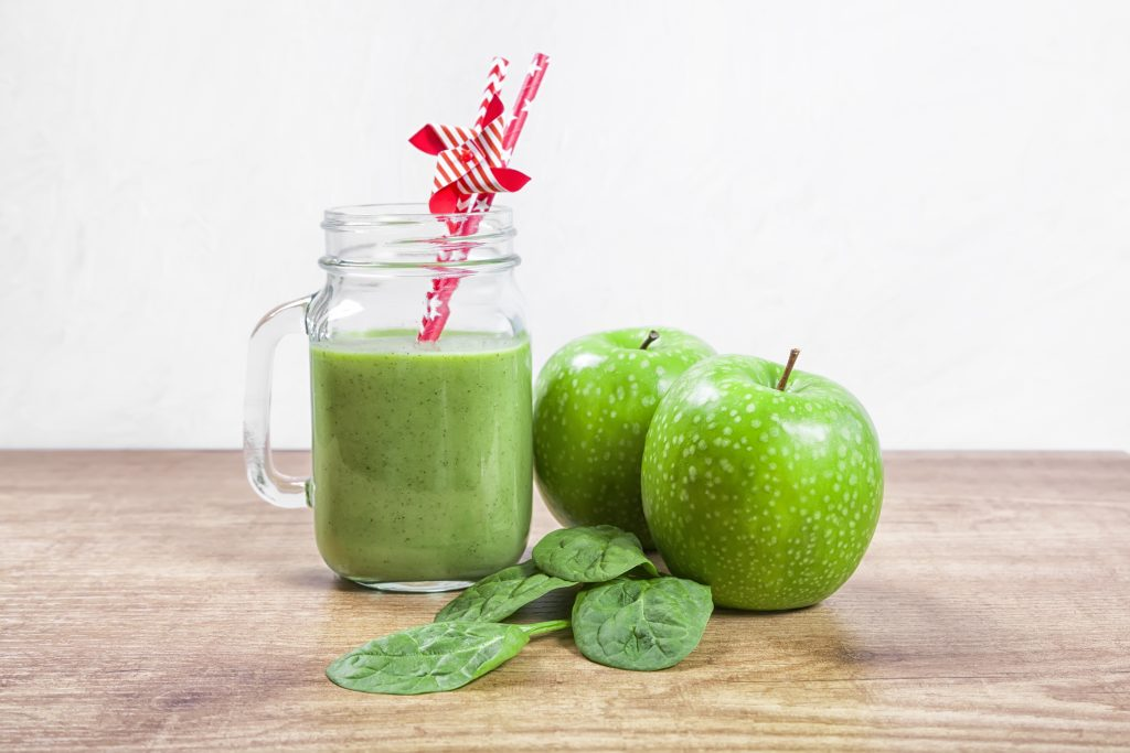 Green smoothie with lime, coconut milk, granny smith apple, baby spinach, yogurt and ice cubes.