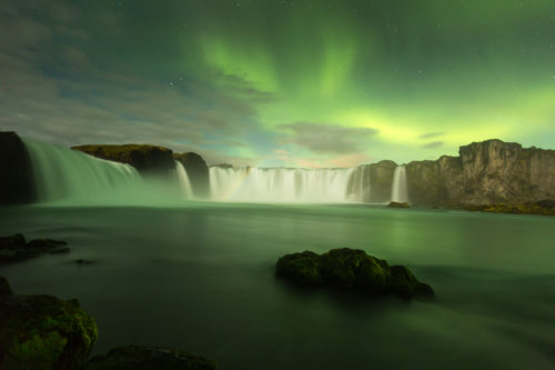 The beautiful green aurora borealis display over the famous Goðafoss waterfall in northern Iceland.