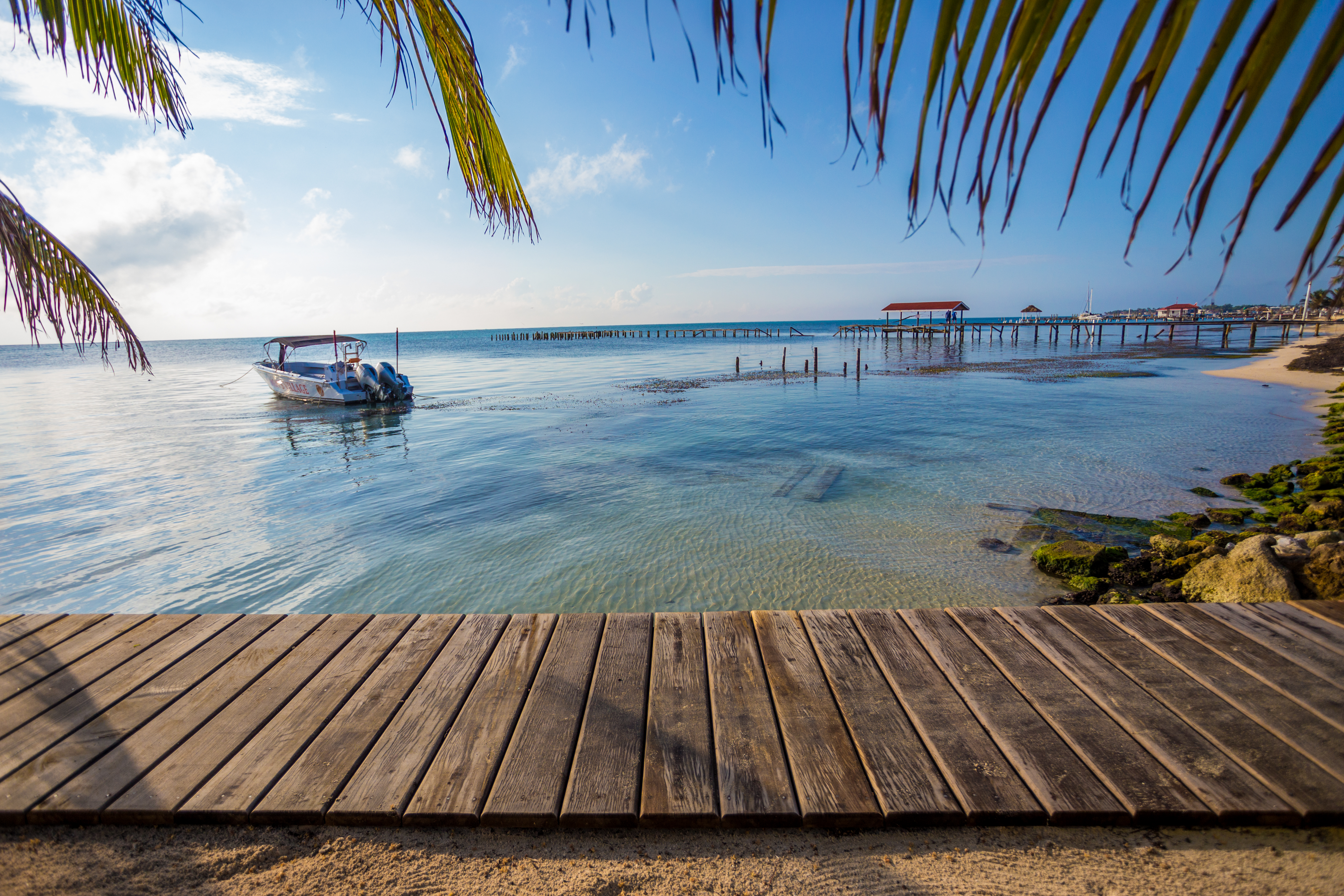 A scenic beach view showing a wooden boardwalk at the waters edge, framed by palm leaves. The crystal clear water against a bright blue sky. A pier damaged by a recent hurricane can also be seen in the background.