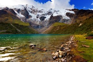 Deserted edge of turquoise Humantay Lake with snowcapped mountains looming in background, sidetrip from Salkantay Trek to Machu Picchu, Peru, autumn evening