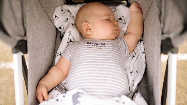 Wandelwagen met baby rolt vijver in terwijl moeder door kledingrek neust
