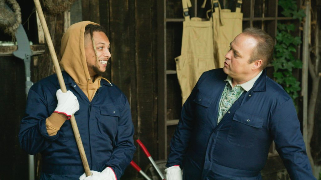 Ronnie en Frans Bauer op een boerderij met een bezem kijken elkaar aan